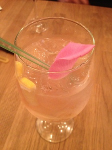 Rose champagne cocktail with flower petal.